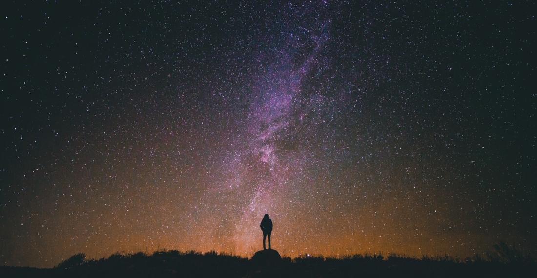 man standing amongst universe stars